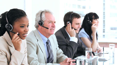 Serious call centre agents talking with headsets Footage