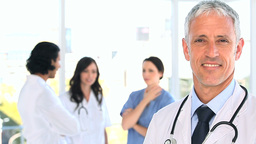 Smiling mature doctor standing in front of his tea Stock Video Footage