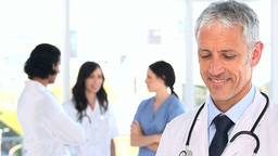 Happy mature doctor standing in front of his team Stock Video Footage