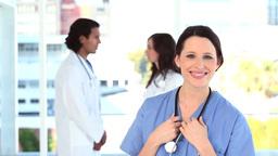 Doctors talking behind a nurse Stock Video Footage