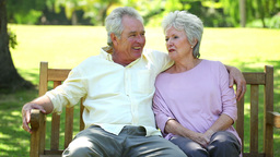 Retired couple sitting on a bench Stock Video Footage