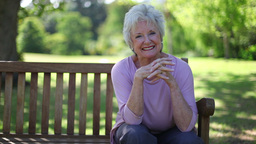 Retired woman smiling while sitting on a bench Footage
