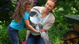 Mother and daughter watering flowers together Footage