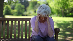 Depressed retired woman sitting on a bench Stock Video Footage