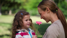 Mother smelling a flower holding by her daughter Stock Video Footage