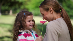 Mother smelling a flower holding by her daughter Footage