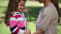 Little girl holding a flower with her mother Footage