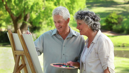 Smiling mature man painting in front of his wife Footage
