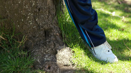 Smiling mature man leaning against a tree in sport Stock Video Footage