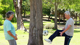 Happy mature couple playing with a soccer ball Footage