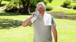 Happy mature man drinking water after doing sport Footage