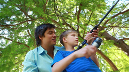 Smiling boy using a fishing rod while being helped by his father Footage