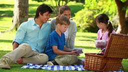 Happy family sitting on a blanket during a picnic Footage