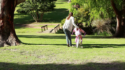Rear view of a woman helping her daughter to ride Stock Video Footage