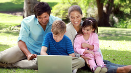 Smiling family sitting on the grass with a laptop Stock Video Footage