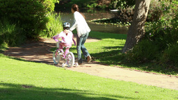 Smiling woman helping her daughter to ride a bike Footage