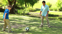 Smiling man playing soccer with his son Footage