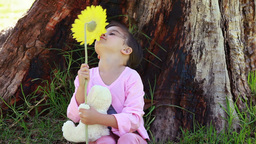 Smiling girl playing with a flower and a teddy bea Footage
