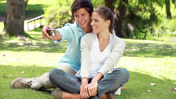 Couple sitting on the grass while photographing th Footage