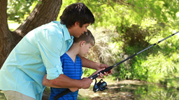 Father and son using a fishing rod together Footage