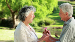 Smiling mature woman being given a flower Footage