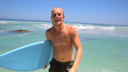 Blonde man holding a blue surfboard Stock Video Footage
