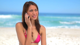 Smiling brunette wearing a bikini while using her Stock Video Footage