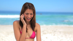 Smiling brunette wearing a bikini while using her  Footage