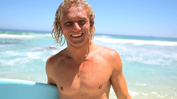 Happy blonde man holding his surfboard Footage