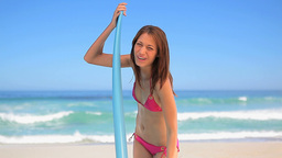 Smiling brunette holding a blue surfboard Footage
