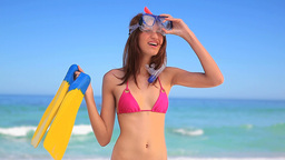 Smiling brunette woman holding a snorkeling equipm Footage