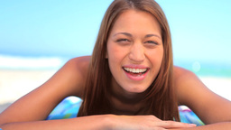 Smiling brunette woman lying on her towel Footage