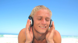 Blonde man bobbing while listening to music Footage