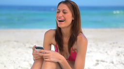 Happy brunette woman sitting while using her cellp Footage