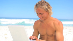 Happy blonde man holding his laptop Stock Video Footage