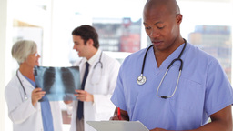 Nurse writing on a clipboard in front of doctors Footage