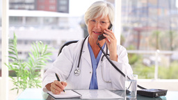 Smiling doctor talking on the phone while sitting Stock Video Footage