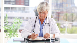 Serious mature doctor writing on her calendar Stock Video Footage