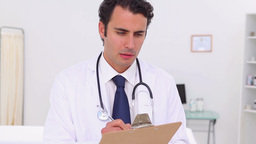 Serious doctor using his clipboard Footage