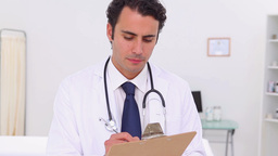 Serious doctor using his clipboard Stock Video Footage