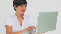 Businesswoman holds a laptop as she types on it Footage
