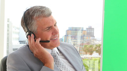 Businessman gesturing while talking on a headset Stock Video Footage