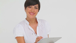 Businesswoman smiling while writing on a clipboard Footage