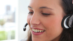 Businesswoman smiles as she talks on a headset Footage