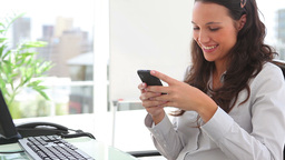 Businesswoman smiling while writing a text message Stock Video Footage