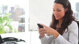 Businesswoman smiling while writing a text message Footage