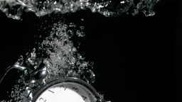 Alarm clock in a super slow motion falling in wate Stock Video Footage
