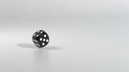 One black dice in a super slow motion rebounding Footage