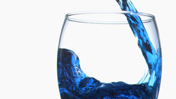 Blue trickle in super slow motion flowing in a glass Footage