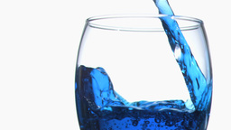 Blue trickle in super slow motion flowing in a gla Stock Video Footage